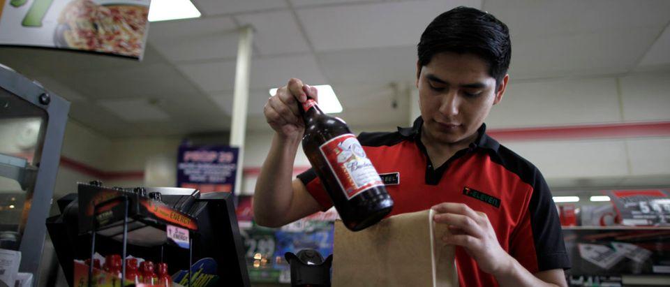 Abel Santiago, 21, serves a customer at a 7-Eleven convenience store in Santa Monica, California April 24, 2012. REUTERS/Lucy Nicholson