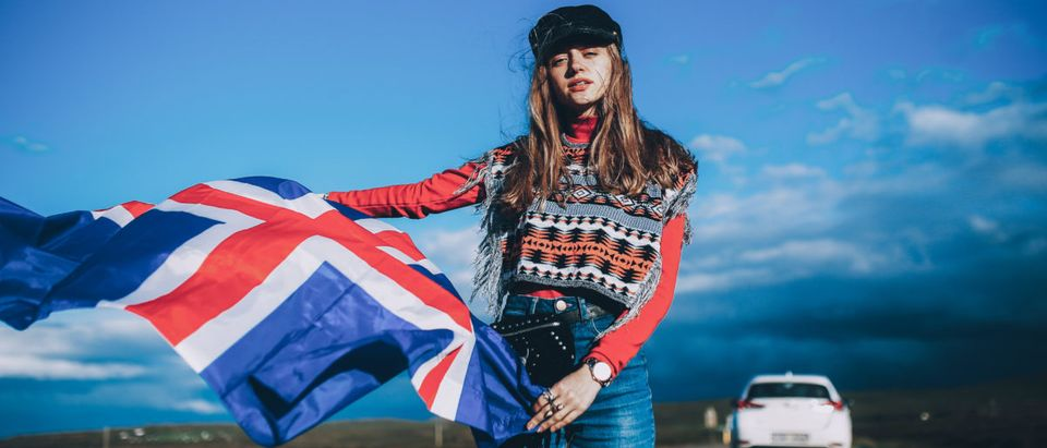 A girl in a colorful cape is pictured with the Iceland flag. (Shutterstock/kondr.konst)