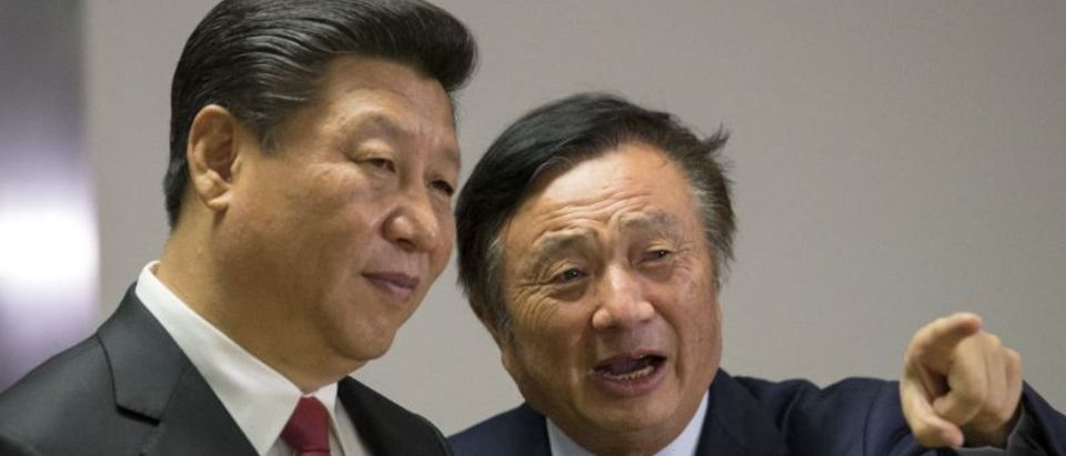 FILE PHOTO: Chinese President Xi Jinping (L) pauses as he is shown around the offices of Huawei Technologies Co Ltd by Ren Zhengfei, president of Huawei, in London, Britain October 21, 2015. REUTERS/Matthew Lloyd/File Photo