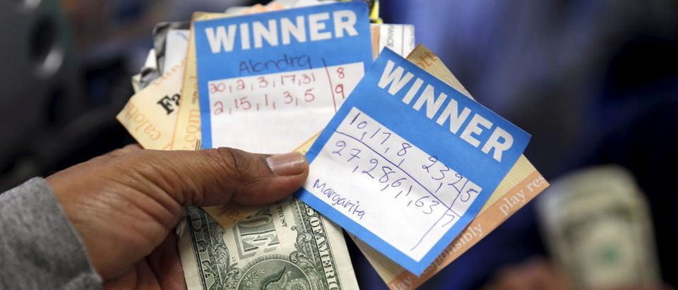 A man holds Powerball lottery ticket numbers chosen by his wife and daughters at Bluebird Liquor in Hawthorne, Los Angeles, California, United States, January 12, 2016. The Powerball Jackpot has reached a record $1.5 billion. REUTERS/Lucy Nicholson