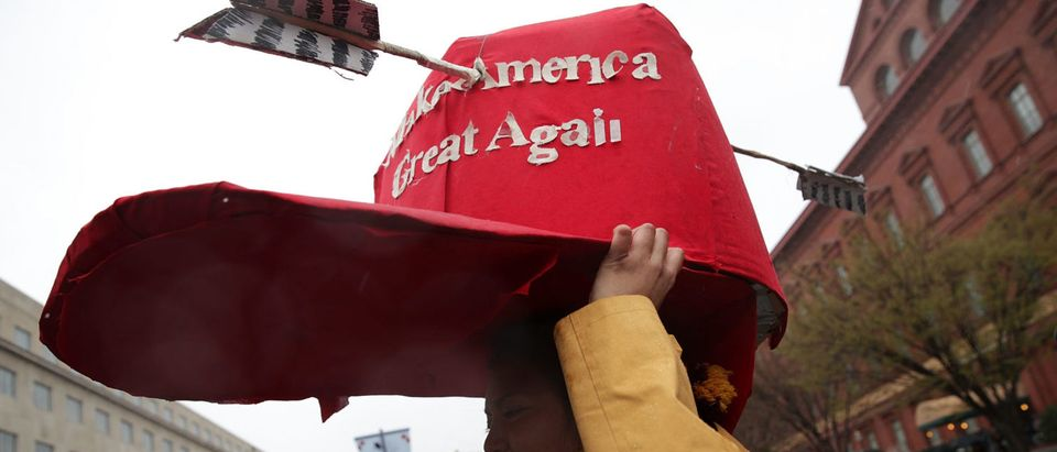 "WASHINGTON, DC - MARCH 10: An activist put a giant ""Make America Great Again"" hat on her head outside the Army Corps of Engineers Office to protest against the Dakota Access Pipeline March 10, 2017 in Washington, DC. The Standing Rock Sioux Tribe held the event with a march to the White House to urge for halting the construction of the project. (Photo by Alex Wong/Getty Images)"