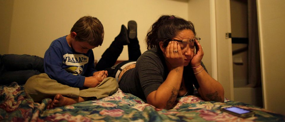 Angelica Cervantes and her son Tomas Cervantes sit in a motel room in Port Hueneme