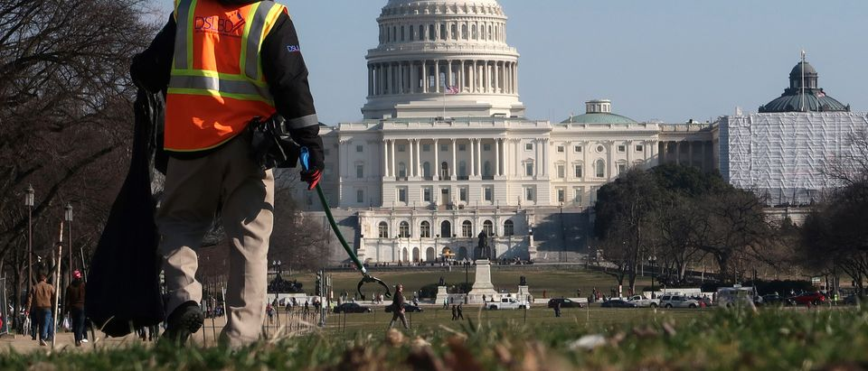 A worker picks up trash on the National Mall near the U.S. Capitol building as the partial government shutdown continues in Washington
