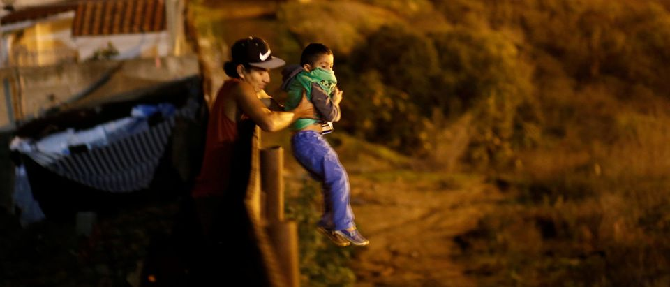 A migrant from Honduras, part of a caravan of thousands from Central America trying to reach the United States, helps a child to jumps the fence to cross it illegally from Mexico into the U.S., in Tijuana, Mexico, January 13, 2019. REUTERS/Mohammed Salem