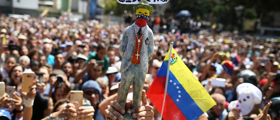"""Supporters of Venezuela's opposition leader Juan Guaido hold a figurine with a sign that reads: """"I fight for freedom"""", during a rally with members of the Venezuela's National Assembly regarding an amnesty law project for members of the military, in Caracas, Venezuela, January 26, 2019. REUTERS/Andres Martinez Casares"""