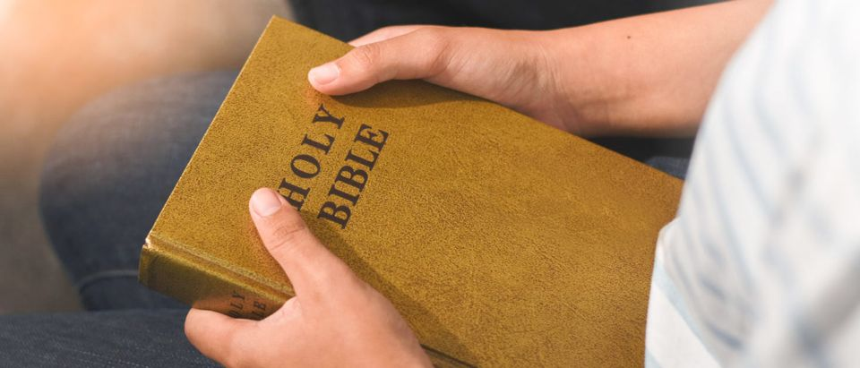 A student is holding a Bible. (Shutterstock/shinphoto)