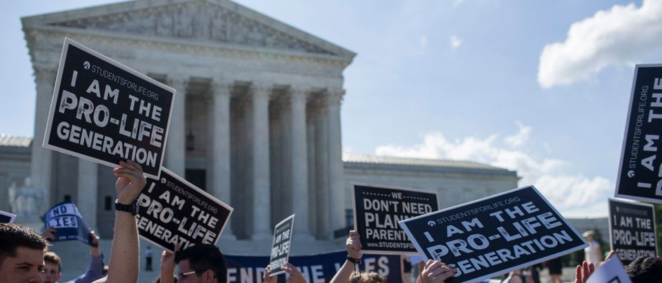 Abortion opponents hold signs in front of the U.S. Supreme Court on June 25, 2018 in Washington, D.C. (Zach Gibson/Getty Images)