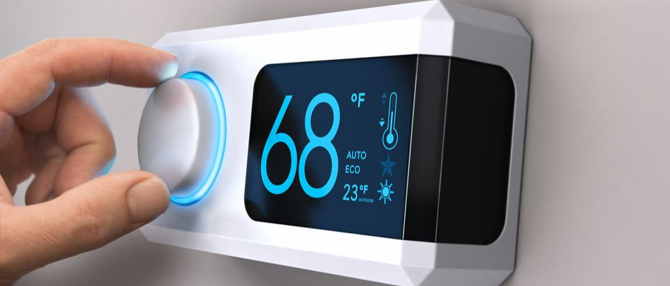 Hand turning a home thermostat knob to set temperature on energy saving mode. (Shutterstock/Olivier Le Moal)