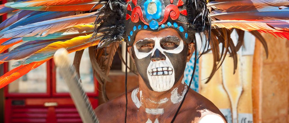 Unknown man in Mayan traditional ornamental feather headdress playing on drums to the ritual pleased the rain god Xipe Totec. July 15, 2011 in Tulum, Quintana Roo, Mexico. (Shutterstock/Patryk Kosmider)