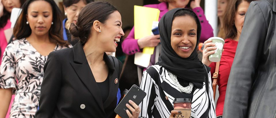 Rep. Alexandria Ocasio-Cortez (D-NY) (L) and Rep. Ilhan Omar (D-MN) (C) join their fellow House Democratic women for a portrait in front of the U.S. Capitol January 04, 2019 in Washington, DC. Chip Somodevilla/Getty Images