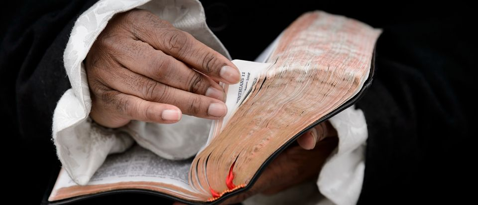 A man looks through scriptures while he and other members of the Black Hebrew Israelites gather on Capitol Hill November 13, 2018 in Washington, DC. - The Black Hebrew Israelites are groups of Black Americans who believe that they are descendants of the ancient Israelites. BRENDAN SMIALOWSKI/AFP/Getty Images