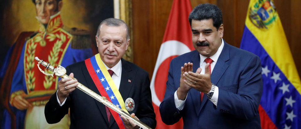 Turkish President Tayyip Erdogan holds a replica of the sword of national hero Simon Bolivar in Caracas