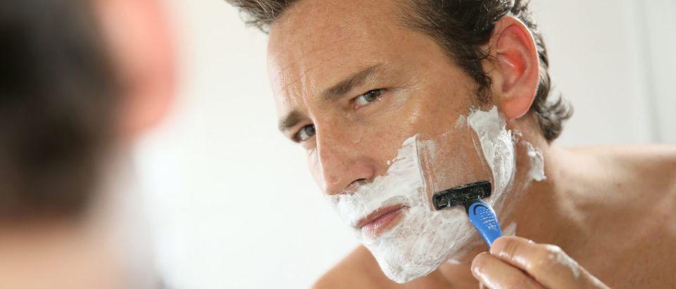 A man shaves. Shutterstock image via user Goodluz