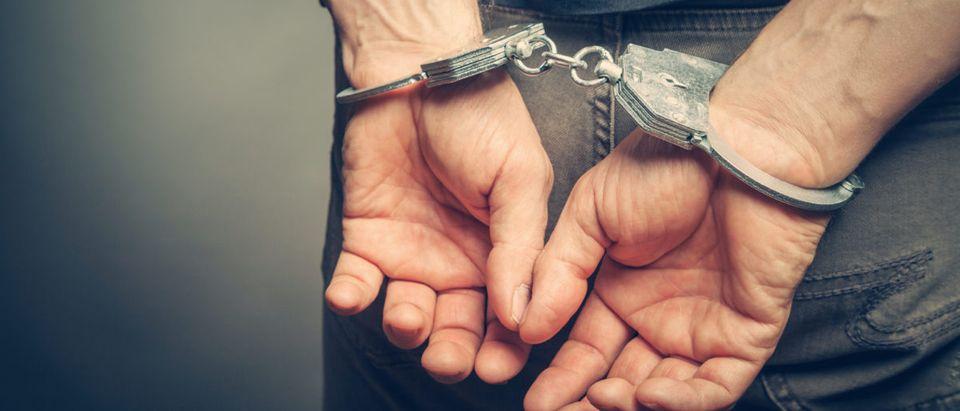 A man is in handcuffs. Shutterstock image via user BortN66