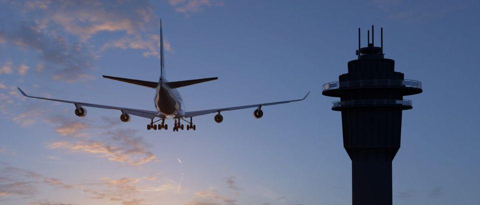 A plane flies by an air traffic control tower. Shutterstock image via user Ralf Maasen