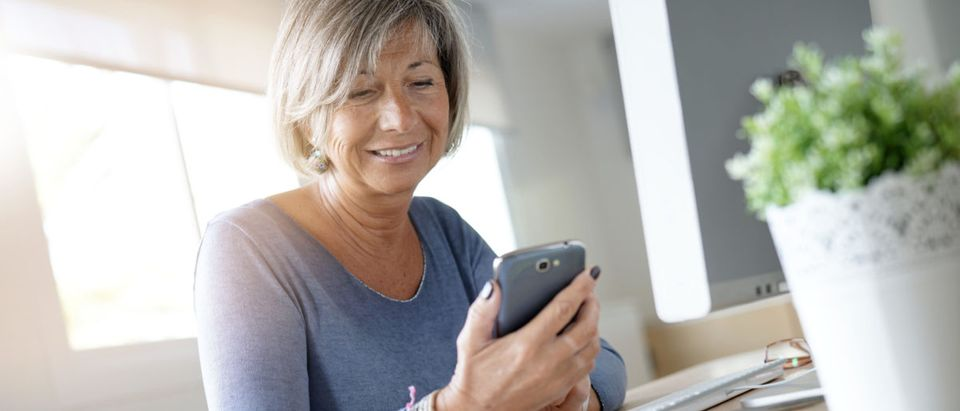 A woman looks at her smartphone. Shutterstock image via user goodluz