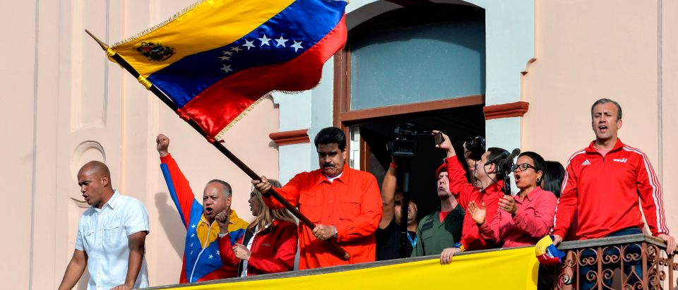 Venezuelan President Nicolas Maduro (C) holds a national flag while speaking to a crowd of supporters (LUIS ROBAYO/AFP/Getty Images)