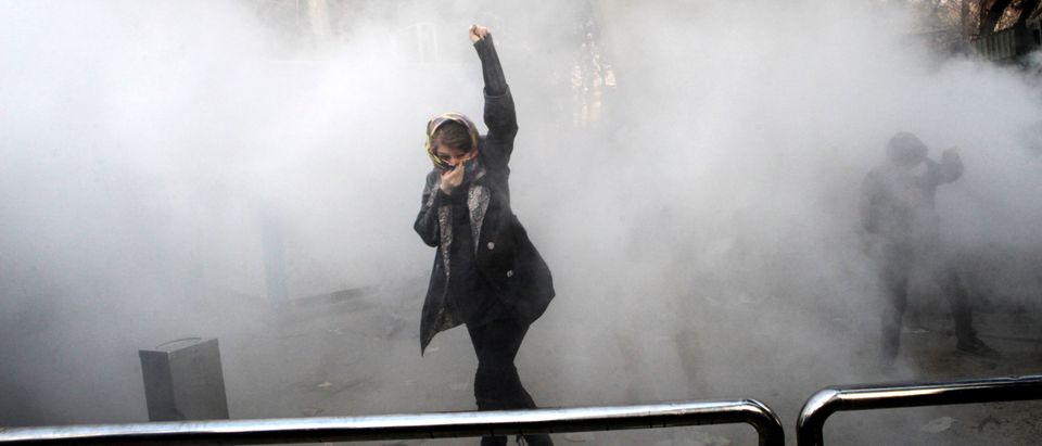 TOPSHOT - An Iranian woman raises her fist amid the smoke of tear gas at the University of Tehran during a protest driven by anger over economic problems, in the capital Tehran on December 30, 2017. (STR/AFP/Getty Images)