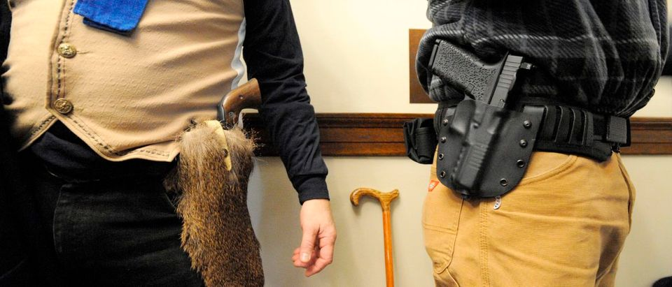 Two men dressed as patriots carry guns during the opening day of the House of Representatives at the New Hampshire State House, where the House will vote on a bill which currently allows people to carry guns in the House Chambers and other parts of the State House in Concord, New Hampshire, on Jan. 2, 2019. (Photo: JOSEPH PREZIOSO/AFP/Getty Images)