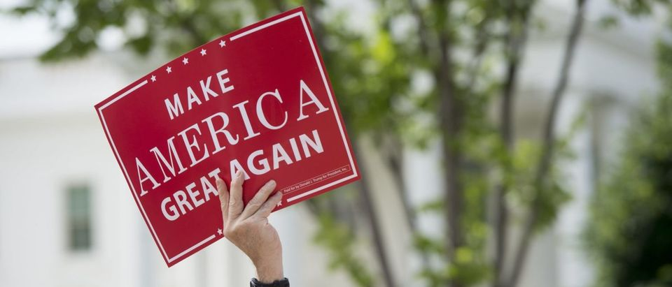 "A man holds a Make America Great Again sign as supporters of US President Donald Trump and his policies demonstrate during a ""Pittsburgh Not Paris"" rally in support of his decision to withdraw the US from the Paris Climate Accord during a rally in Lafayette Square next to the White House in Washington, DC, on June 3, 2017. / AFP PHOTO / SAUL LOEB / Getty Images"