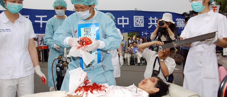 Taipei, TAIWAN: During a rally joined by thousands of Falun Gong practitiioners at Taipei 23 April 2006, four demonstrators play in an action drama against what they said was the Chinese communists' killing of Falun Gong followers and harvesting of their organs in concentration camps. (PATRICK LIN/AFP/Getty Images)
