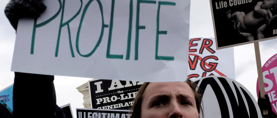 FILE PHOTO: A counter-protester holds an anti-Trump sign behind an anti-abortion demonstrator as the annual March for Life concludes at the U.S. Supreme Court in Washington