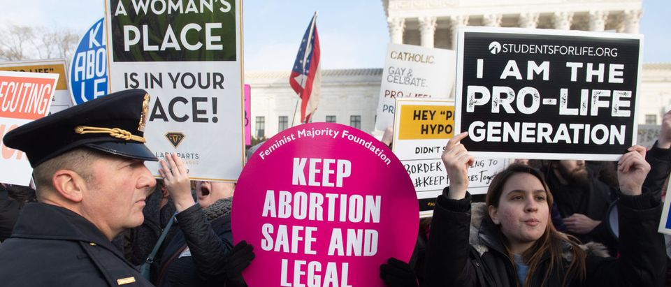 Pro-choice activists hold signs in response to pro-life activists participating in the March for Life outside the U.S. Supreme Court in Washington, D.C. on January 18, 2019. (Saul Loeb/AFP/Getty Images)