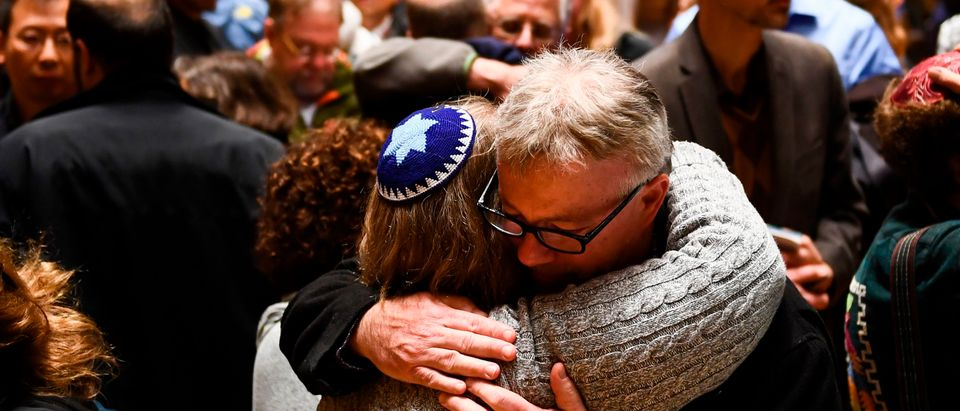 People hug after a vigil, to remember the victims of the shooting at the Tree of Life synagogue the day before, at the Allegheny County Soldiers Memorial on October 28, 2018, in Pittsburgh, Pennsylvania. (BRENDAN SMIALOWSKI/AFP/Getty Images)