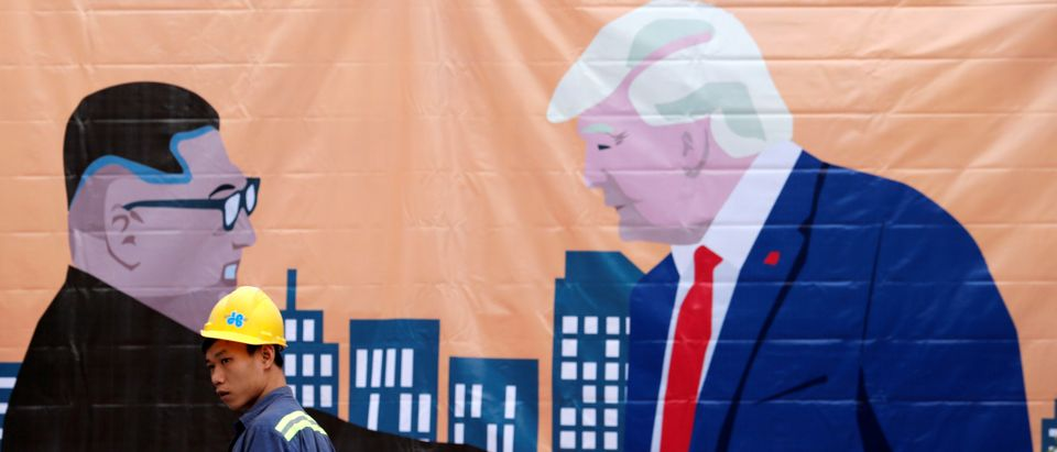 A man walks past a banner depicting North Korean leader Kim Jong Un and U.S. President Donald Trump ahead of the North Korea-U.S. summit in Hanoi