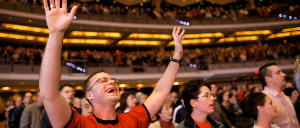 A parishioner cries as he signs a song of worship in the 7,000-seat Willow Creek Community church during a Sunday service in South Barrington, Illinois, November 20, 2005. REUTERS/John Gress