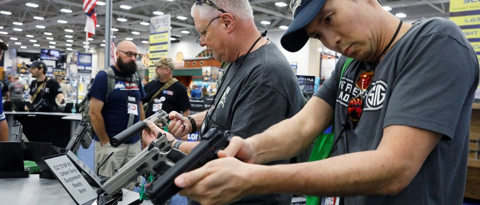 Gun enthusiasts inspect firearms during the annual National Rifle Association (NRA) convention in Dallas, Texas