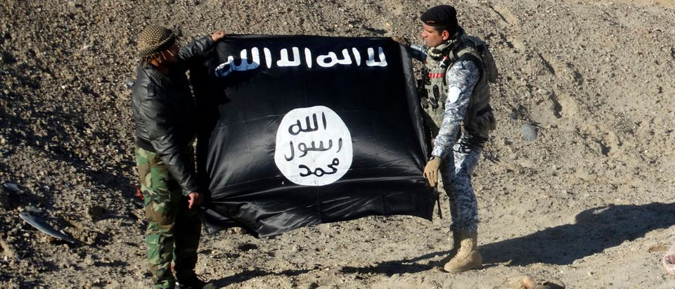 Iraqi security forces hold an Islamist State flag near the bodies of dead members of the Islamic State in the outskirt of Ramadi December 23, 2014. Picture taken December 23, 2014. REUTERS/Stringer