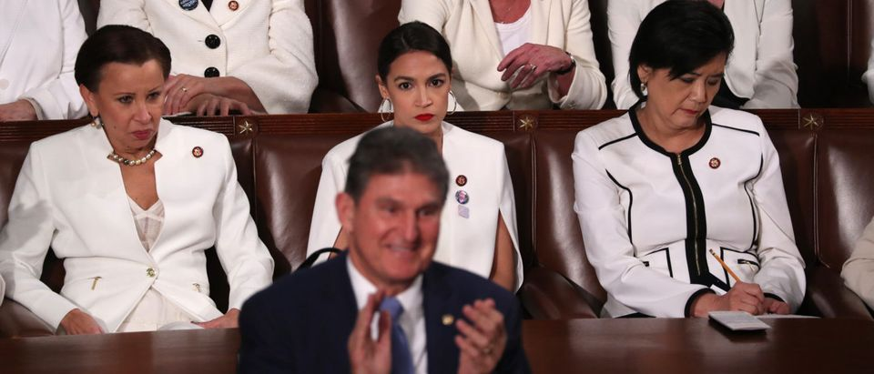 Democratic women of the U.S. House of Representatives, including Rep. Alexandria Ocasio-Cortez (D-NY) (C), remain in their seats as Senator Joe Manchin (D-WV) stands and applauds in front of them as U.S. President Donald Trump delivers his second State of the Union address. REUTERS/Jonathan Ernst