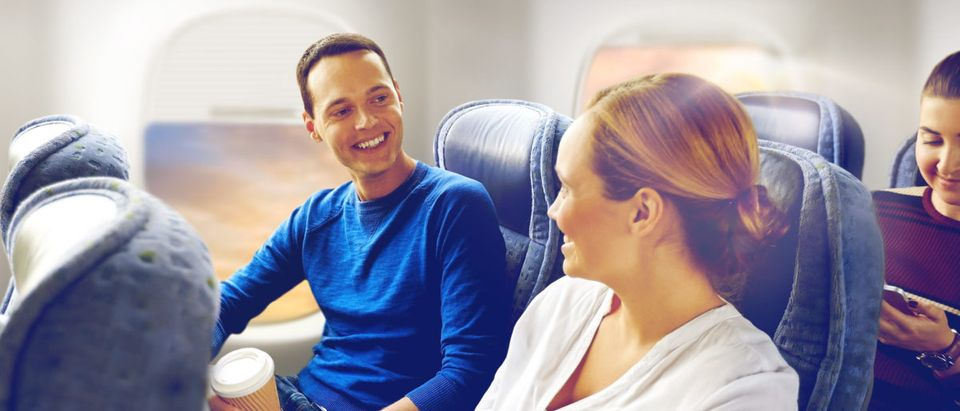 A man and woman chat on a plane. Shutterstock image via user Syda Productions
