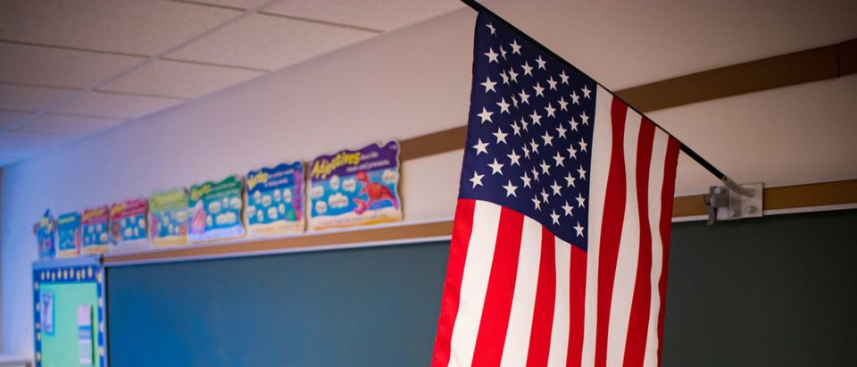An American flag is in a classroom. Shutterstock image via user Tom DeCicco