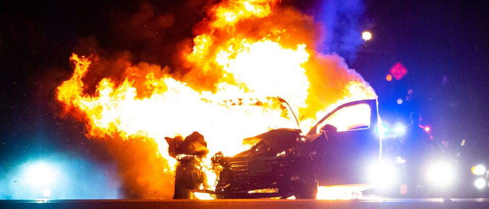 Police respond to a burning car (Shutterstock/Photo Spirit)