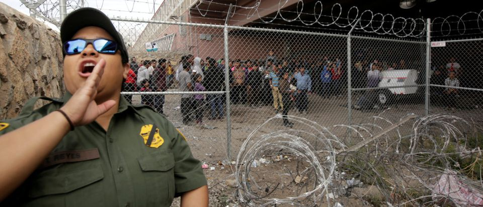 FILE PHOTO: A U.S. CBP officer reacts near an enclosure where Central American migrants are being held after turning themselves in to request asylum, in El Paso