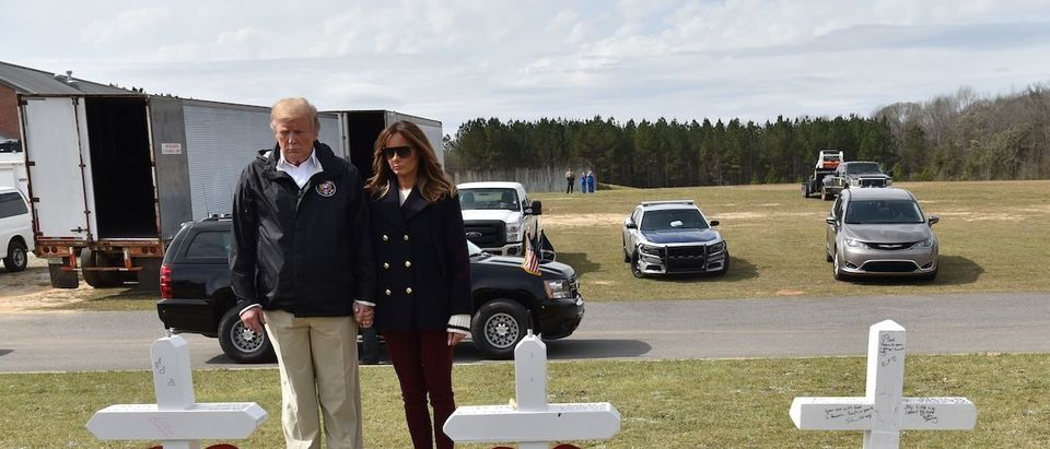 US President Donald Trump and First Lady Melania Trump stand before a row of crosses honoring 23 people who died in the storm outside Providence Baptist Church March 8, 2019 in Opelika, Alabama, during a tour of tornado-damaged areas in the southern US state. (Photo credit:NICHOLAS KAMM/AFP/Getty Images)