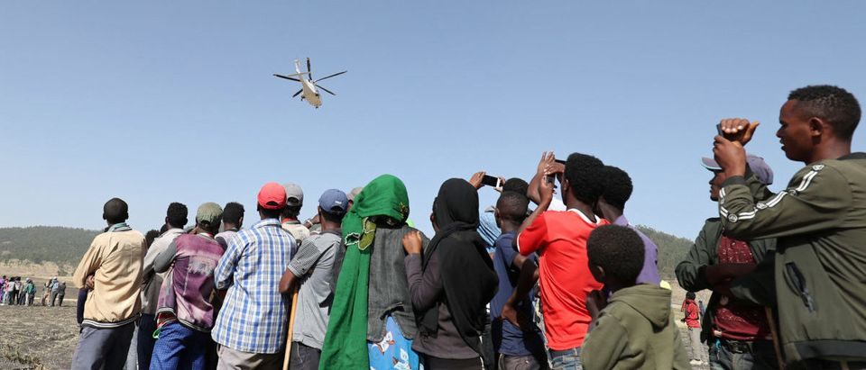 Civilians watch as a helicopter leaves the scene of the Ethiopian Airlines Flight ET 302 plane crash, near the town of Bishoftu, southeast of Addis Ababa, Ethiopia March 11, 2019. REUTERS/Tiksa Negeri