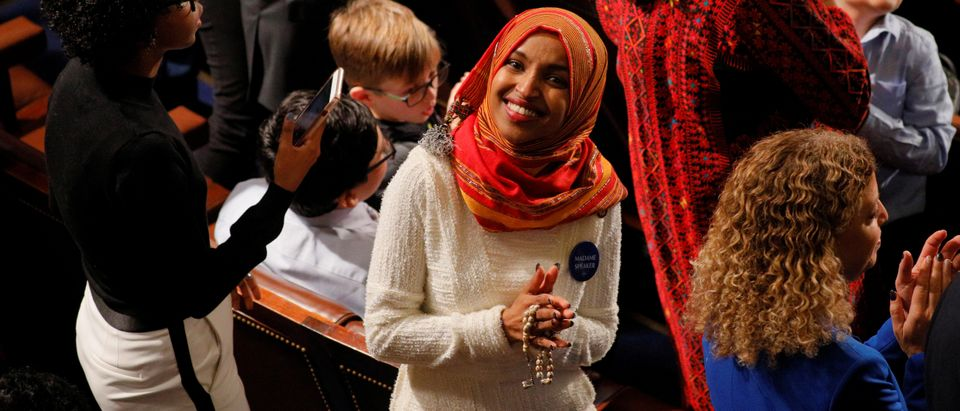 Ilhan Omar smiles from the floor of the U.S. House of Representatives before being sworn in to the new Congress at the U.S. Capitol in Washington