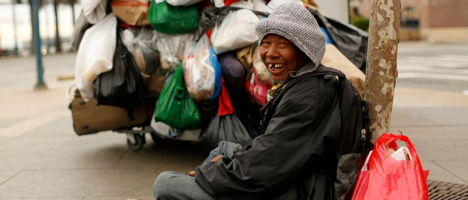 A man named Dong, who said he is homeless, smiles as he sits with his possessions along The Embarcadero in San Francisco, California March 16, 2015. REUTERS/Robert Galbraith