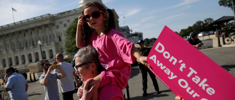 A girl is carried as healthcare activists protest in opposition to the Senate Republican healthcare bill on Capitol Hill in Washington