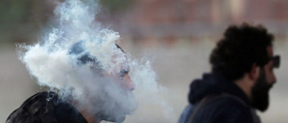 A cloud of vapour from an electronic cigarette is exhaled by a man on a street in downtown Cairo, Egypt February 9, 2019. REUTERS/Amr Abdallah Dalsh