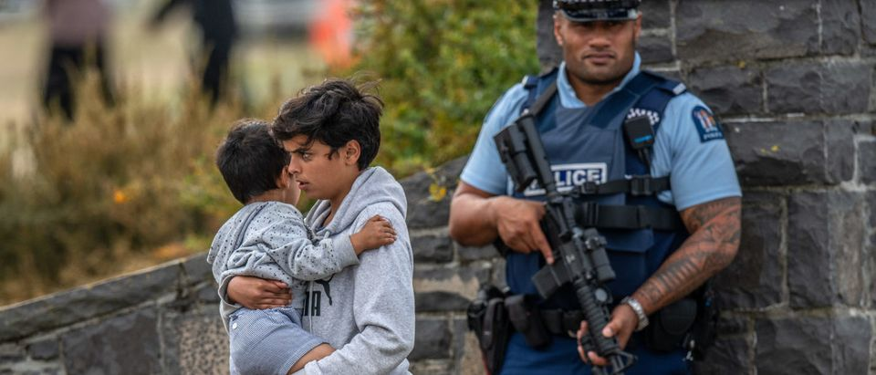 CHRISTCHURCH, NEW ZEALAND - MARCH 20: An armed policeman looks on as a youngster is carried by a boy as they leave Memorial Park Cemetery after attending a funeral for two of the victims of the Christchurch attack on March 20, 2019 in Christchurch, New Zealand. (Photo by Carl Court/Getty Images)