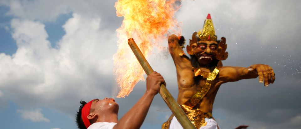 A Balinese Hindu blows fire, during a parade carrying Ogoh-ogoh effigies symbolising evil spirits, during a ritual before Nyepi, the day of silence, in Palembang, South Sumatra province, Indonesia March 8, 2016. REUTERS/Darren Whiteside