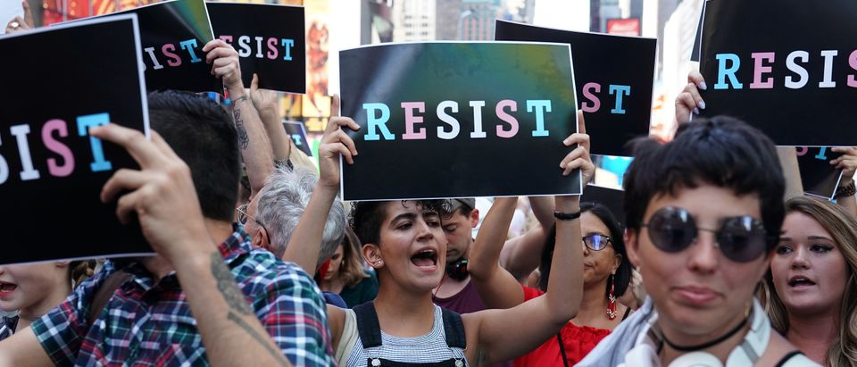 People attend a protest against U.S. President Donald Trump's announcement that he plans to reinstate a ban on transgender individuals from serving in any capacity in the U.S. military, in Times Square, in New York City