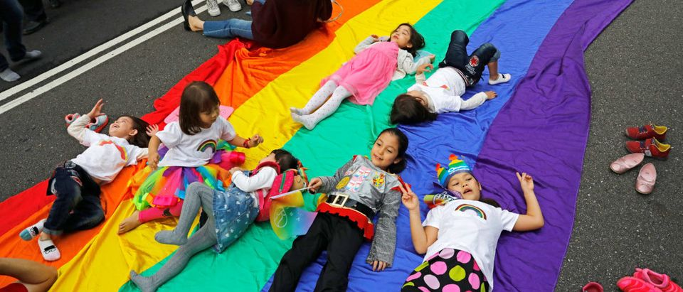 Children play on a giant rainbow flag as they take part in LGBT pride parade in Taipei / Reuters.com
