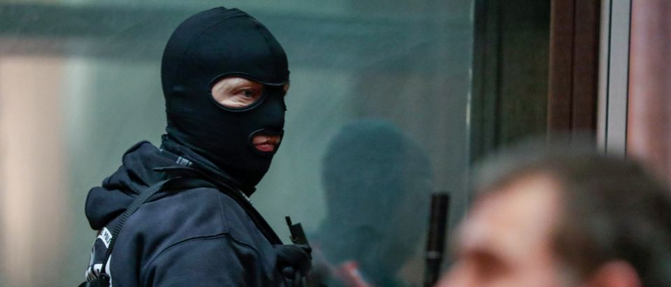 A masked Belgian police officer is seen during the trial of Nemmouche and Bendrer at Brussels' Palace of Justice