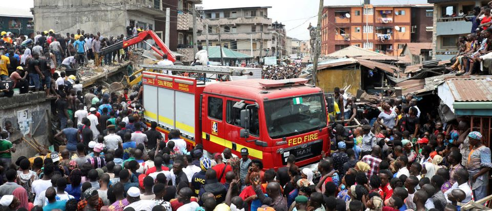 People gather as rescue workers search for survivors at the site of a collapsed building containing a school in Nigeria's commercial capital of Lagos
