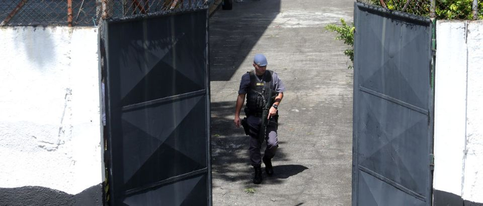 Policeman is seen in the entrance of the Raul Brasil school after a shooting in Suzano